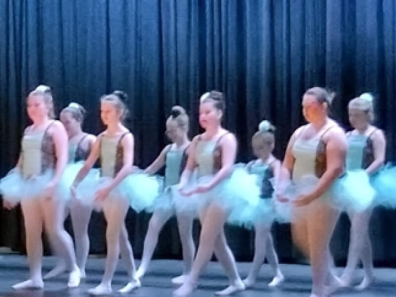 A group of McDowell Choices kids are performing ballet on a stage with a blue curtain backdrop.